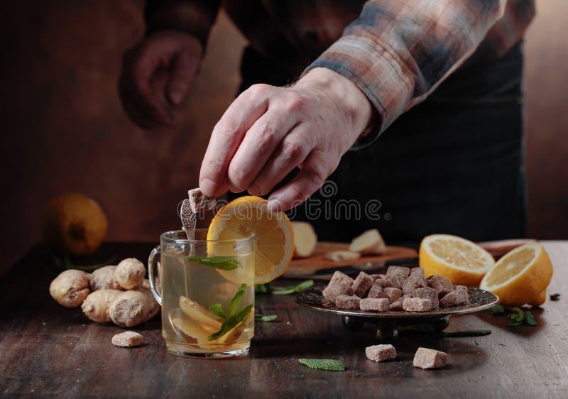 Kop van gemberthee met bruine suiker, citroen en munt op oude houten lijst royalty-vrije stock fotografie