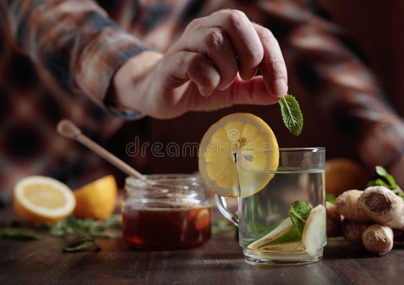 Kop van gemberthee met honing, citroen en munt op oude houten lijst royalty-vrije stock fotografie