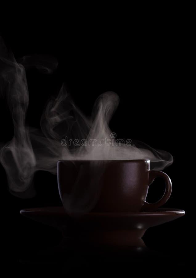 Kop van geurige hete drank met stoom die op zwarte wordt geïsoleerd royalty-vrije stock foto