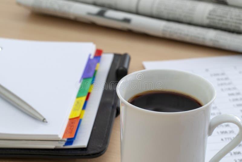Kop van geurige koffie op ochtenddocument bedrijfsnieuws stock fotografie