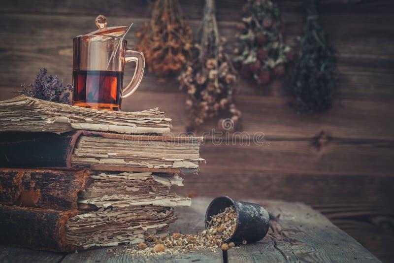 Kop van gezonde thee, mortier van kruiden en oude boeken Hangende bossen van geneeskrachtige kruiden op achtergrond royalty-vrije stock afbeeldingen