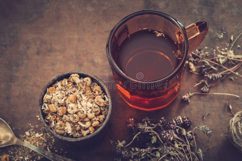 Kop van gezonde thee, rustiek mortier van madeliefjekruiden, droge thyme op lijst royalty-vrije stock afbeeldingen