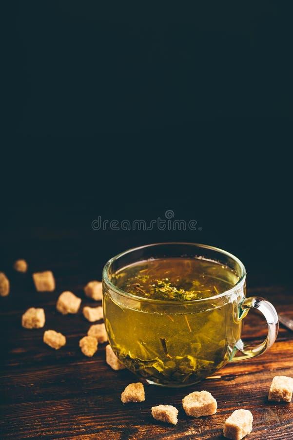 Kop van groene thee met bruine theesuiker royalty-vrije stock foto's