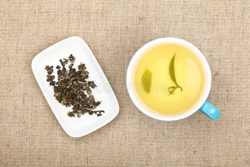Kop van groene thee op canvastafelkleed stock foto's