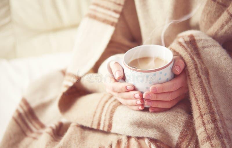 Kop van het hete koffie verwarmen in de handen van een meisje royalty-vrije stock foto's