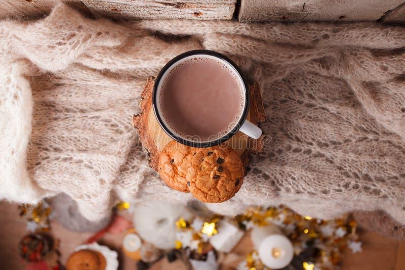 Kop van hete cacao op rustieke houten bank met het breien van zachte sjaal, close-upfoto van warme sweater met Amerikaanse koekje stock fotografie