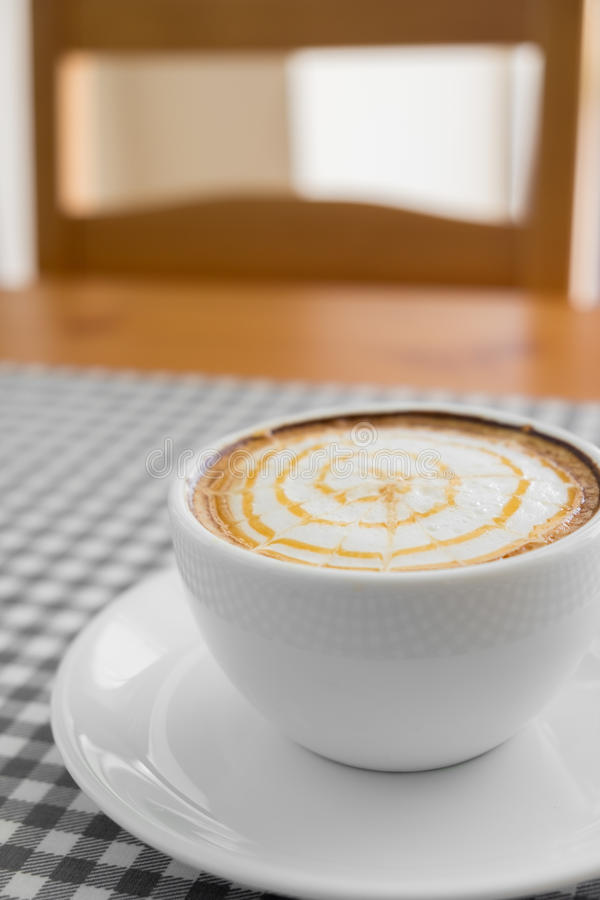 Kop van hete Cappuccinokoffie met Latte-Kunst op plaidlijst royalty-vrije stock foto's