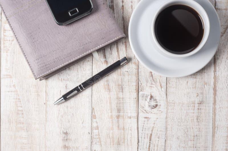 Kop van hete koffie en wit notaboek op houten lijst royalty-vrije stock afbeeldingen