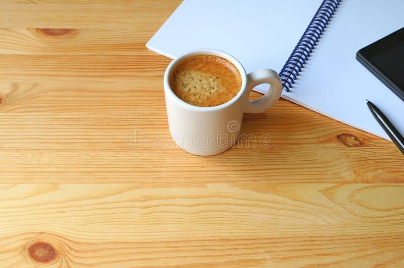 Kop van Hete Koffie met een Notitieboekje en Cellphone op Houten Werkend Bureau royalty-vrije stock foto