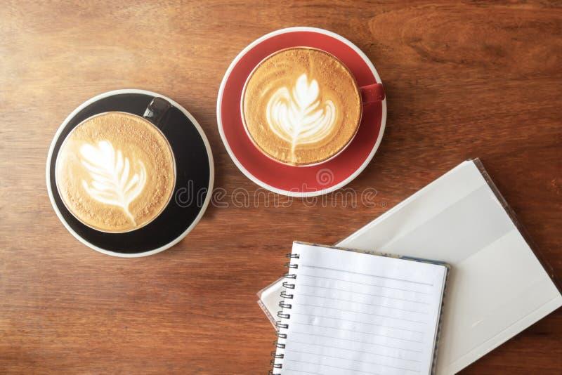 Kop van hete koffie met lattekunst in bladvorm en leeg boek Hoogste mening met exemplaarruimte op houten lijst Uitstekende kleure stock afbeelding