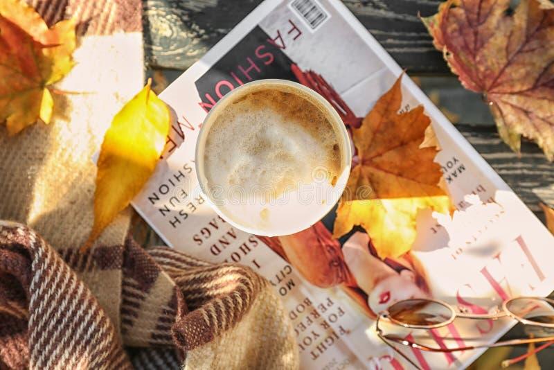 Kop van hete koffie met tijdschrift en de herfstbladeren op houten bank stock foto