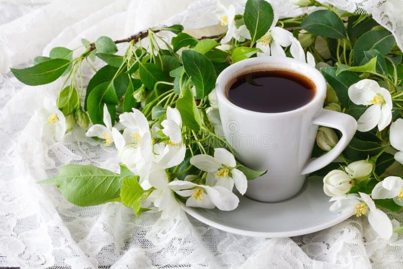 Kop van hete smakelijke koffie in zeer de lente het bloemen plaatsen Hoogtepunt van witte en zeer leuke roze kleur Romantische de royalty-vrije stock fotografie
