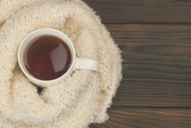 Kop van hete thee gekleed in gebreide warme de wintersjaal, warme gebreide sweater of deken stilleven van een sjaal en een Kop th royalty-vrije stock foto