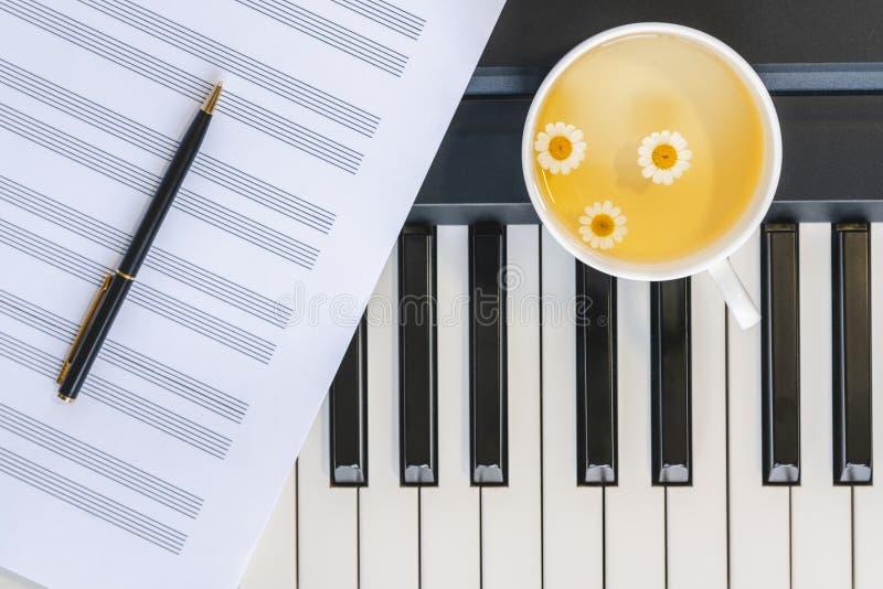 Kop van Kamillethee op een Piano, een Muziekblad en een Pen De hoogste mening, sluit omhoog Stilleven, Concept royalty-vrije stock foto's