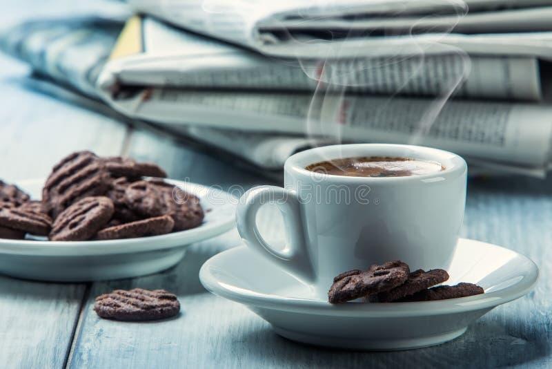 Kop van koffie, chocoladekoekjes en de achtergrondkrant Rook die van de kop toenemen royalty-vrije stock afbeelding