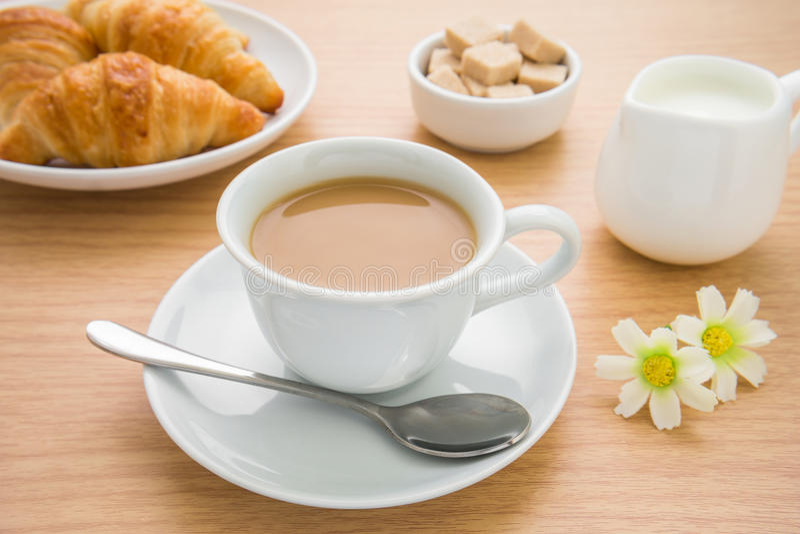 Kop van koffie, croissants, melkkruik en suiker op lijst royalty-vrije stock foto's