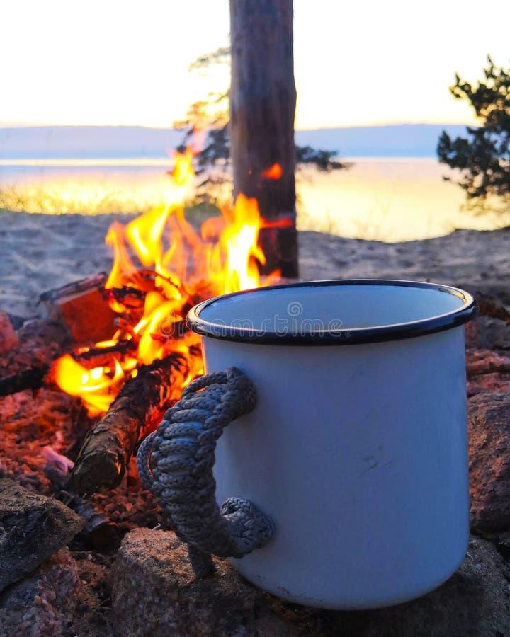 Kop van Koffie door een Kampvuur witte ijzermok door de brand tegen de zonsondergang door het meer royalty-vrije stock afbeelding