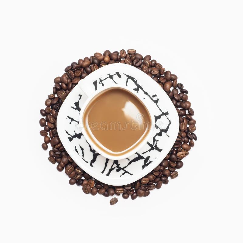 Kop van koffie door koffiebonen die wordt omringd royalty-vrije stock afbeelding