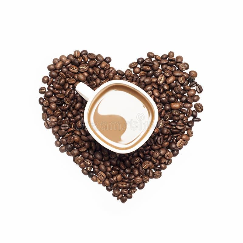 Kop van koffie door koffiebonen wordt omringd in vorm van hart dat stock foto