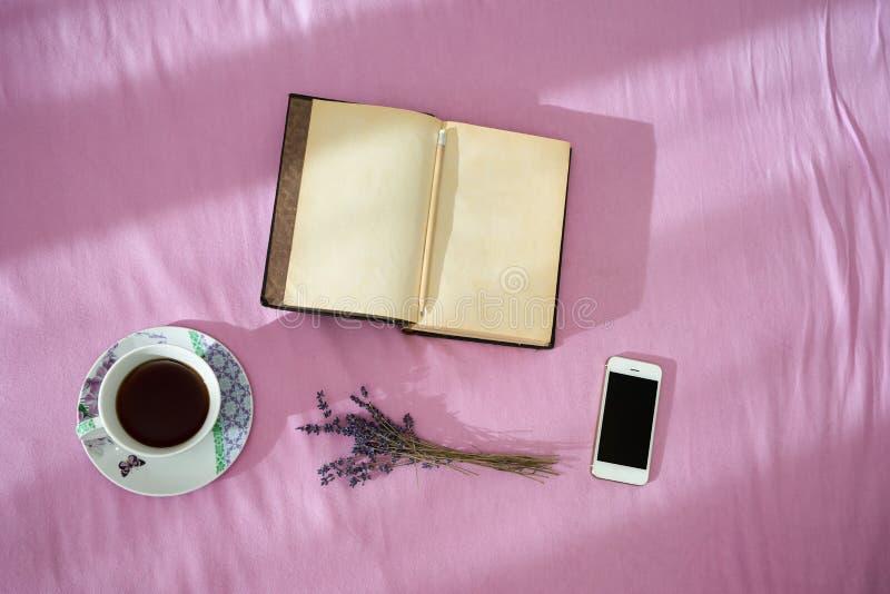 Kop van koffie, droge lavendel, uitstekende notitieboekje en smartphone ove royalty-vrije stock fotografie