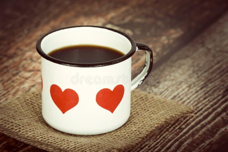 Kop van koffie in een oude emailmok stock fotografie