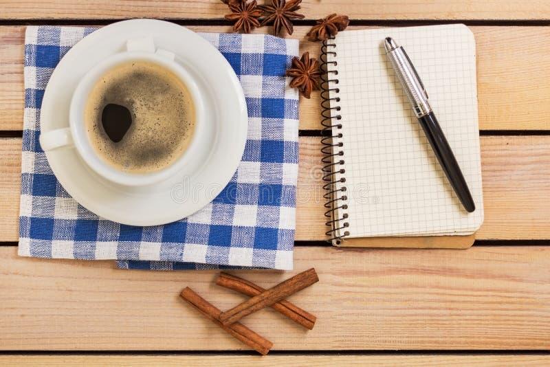 Kop van koffie en blocnote met pen op houten achtergrond royalty-vrije stock foto