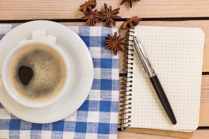 Kop van koffie en blocnote met pen op houten achtergrond royalty-vrije stock afbeelding