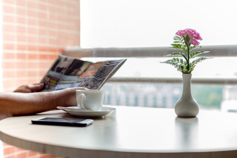 Kop van koffie en celtelefoon met zakenman die een newspape lezen stock afbeeldingen