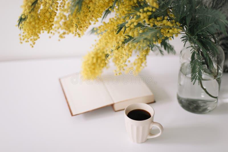 Kop van koffie en een boek op wit bureau met boeketmimosa Planning en ontwerp concept werkplaats Hoogste mening Comfortabel ontbi stock foto