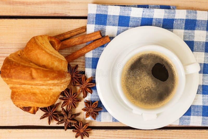 Kop van koffie en een croissantbroodje op een houten achtergrond stock fotografie