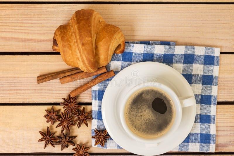 Kop van koffie en een croissantbroodje op een servet op een houten achtergrond royalty-vrije stock foto