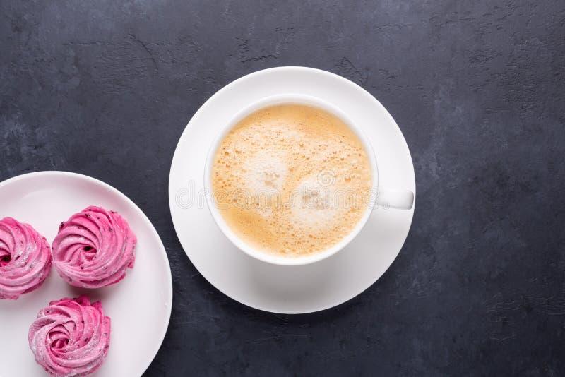 Kop van koffie en eigengemaakte roze heemst op zwarte steenachtergrond royalty-vrije stock fotografie