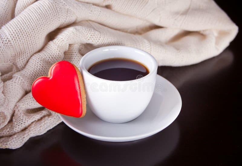 Kop van koffie en hart gevormd koekje op de houten lijst stock foto's