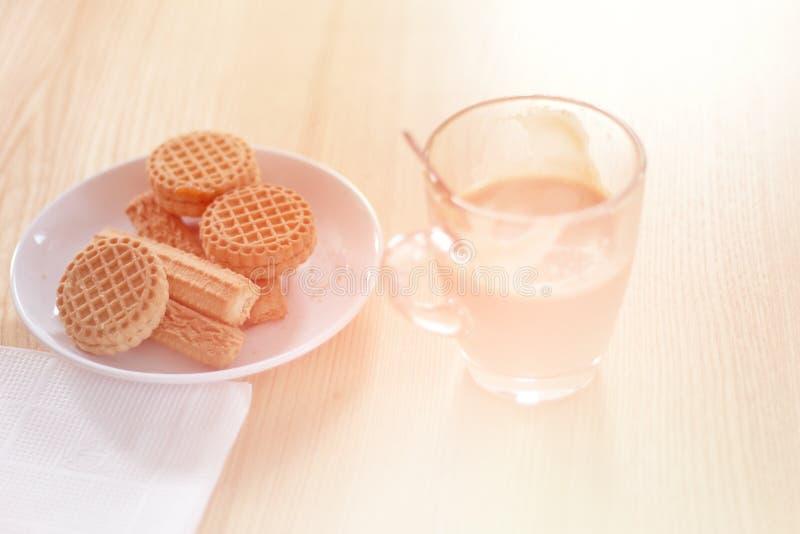 Kop van koffie en koekje op jute en houten lijst, het lichte stemmen royalty-vrije stock fotografie