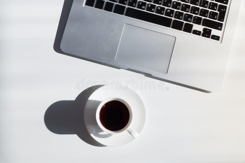 Kop van koffie en laptop computer op witte lijst, hoogste mening stock foto