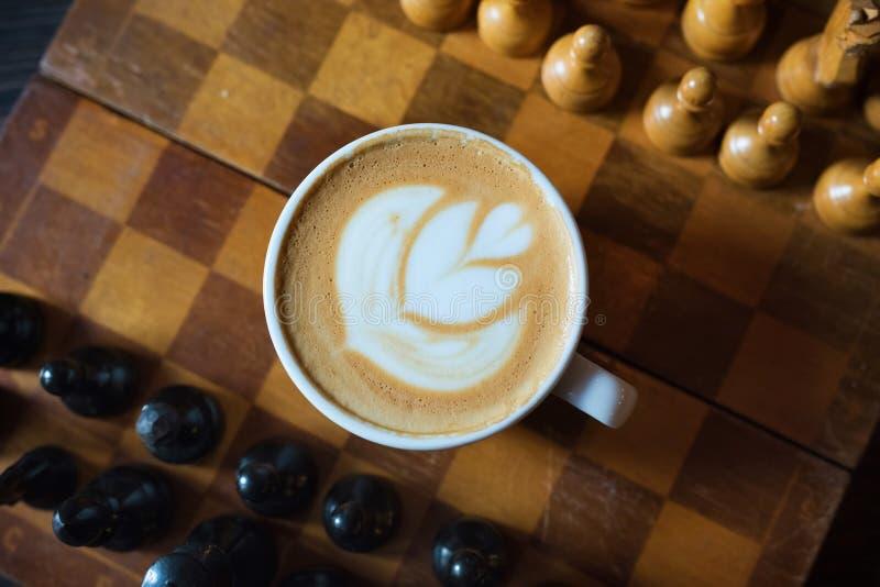 Kop van koffie en schaakbord door close-up op een houten achtergrond Soort van hierboven cappuccino stock afbeelding