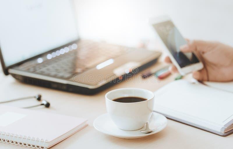 Kop van koffie en slimme telefoon met hand van de bedrijfsmens die laptop computer met behulp van stock foto