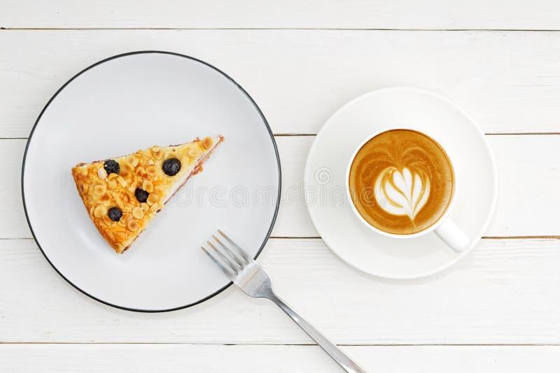 Kop van koffie en stuk van eigengemaakte die cake met kwarksoufflé met amandelen en bosbessen op witte houten lijst wordt verfraa stock afbeelding