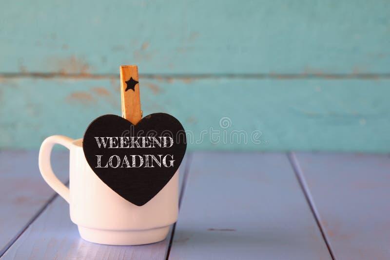 Kop van koffie en weinig bord van de hartvorm met de uitdrukking: WEEKENDlading stock foto