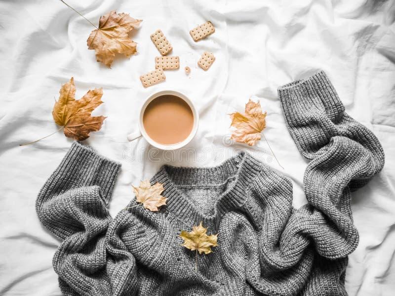 Kop van koffie, grijze warme gebreide sweater overmaatse, gele droge bladeren op het bed - comfortabel huisstilleven, hoogste men stock afbeelding