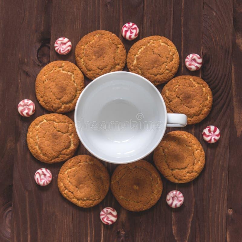 Kop van koffie, havermeelkoekjes en suikergoed op houten achtergrond aan stock fotografie