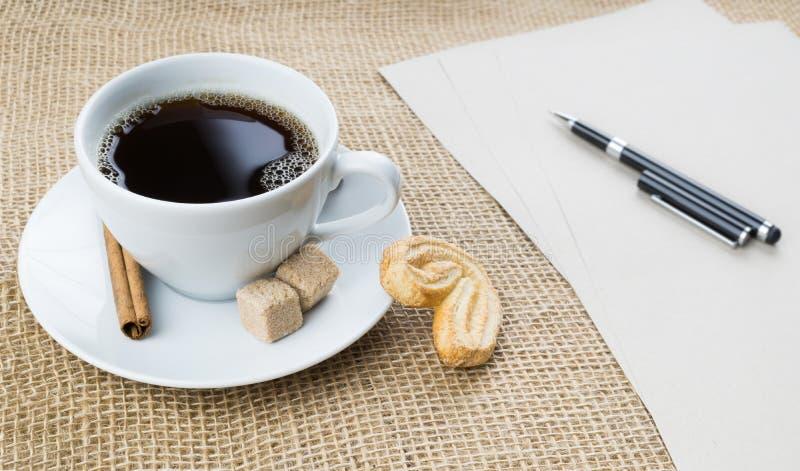 Kop van koffie, koekje, pen en document op juteachtergrond royalty-vrije stock afbeeldingen