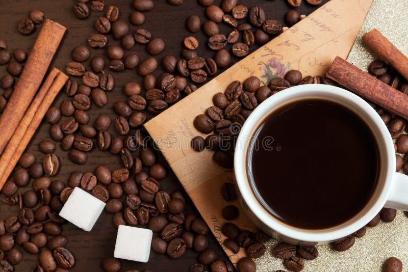 Kop van koffie, koffiebonen, suikerkubussen en kaneel royalty-vrije stock foto
