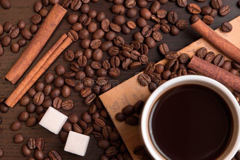 Kop van koffie, koffiebonen, suikerkubussen en kaneel stock foto