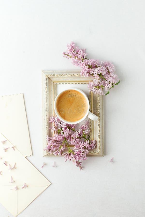 Kop van koffie, lilac tak en kader op witte achtergrond Vlak leg, hoogste mening, exemplaarruimte, huwelijk, vrouwelijk ochtendon royalty-vrije stock foto