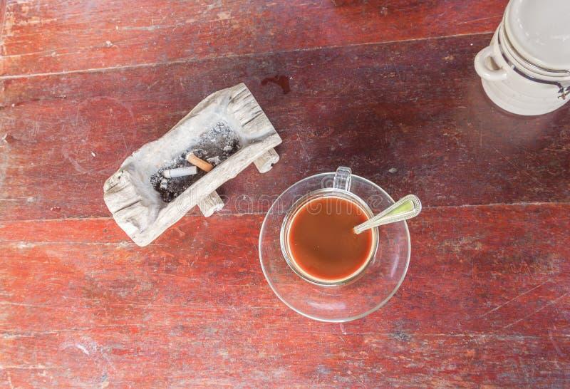 Kop van koffie met asbakjesigaret op houten stock foto's
