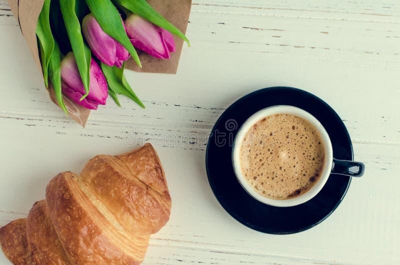 Kop van koffie met boeket van roze tulpen en croissant royalty-vrije stock fotografie