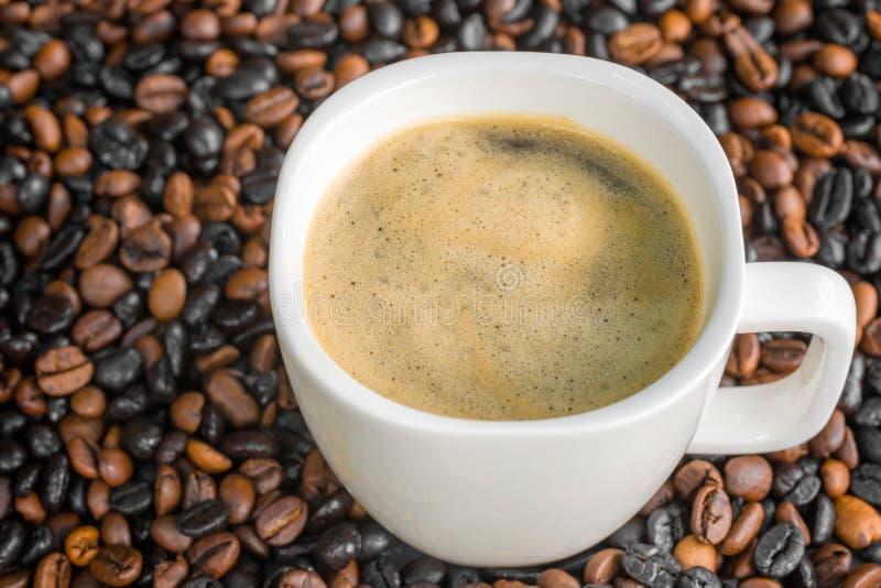 Kop van koffie met bonen op de achtergrond royalty-vrije stock afbeelding