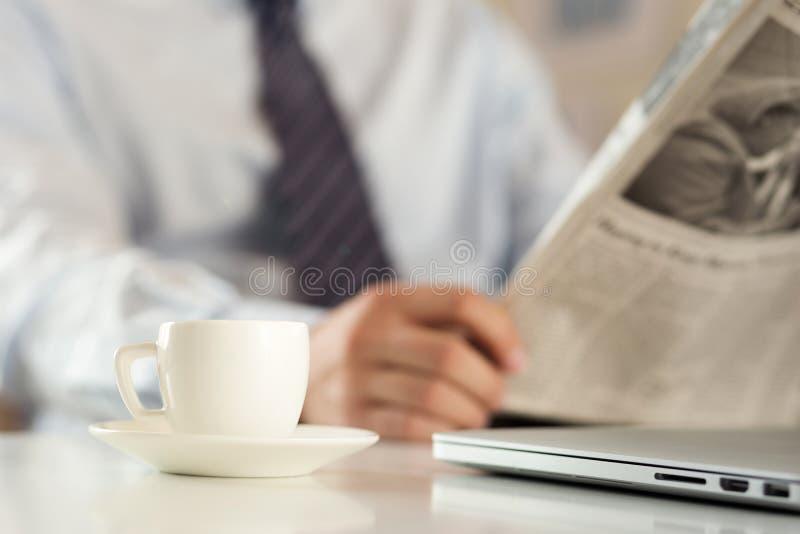Kop van koffie met de krant van de zakenmanlezing op achtergrond stock afbeeldingen