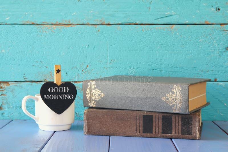 Kop van koffie met een klein bord van de hartvorm met de uitdrukking: GOEDEMORGEN naast stapel oude boeken stock foto